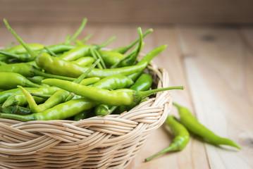 Green peppers in wicker basket on wooden background