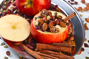 Red juicy apple with assorted nuts , raisins and cinnamon