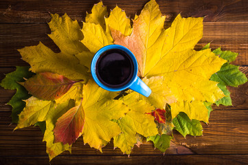 Autumn leaves, hot steaming cup of coffee on wooden table background