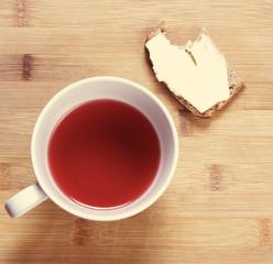 на деревяном столе стоит компот и бутерброд с маслом завтрак