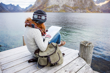 Girl sits on a wooden pier and looking for a route on a map. In the hands of a woman's smartphone.