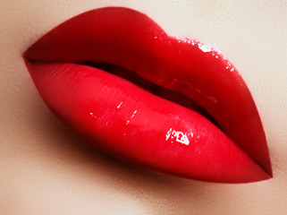 Beauty female face. Professional glossy lip makeup. Pink lip gloss and lipstick. Sensual female mouth. Perfect model's lips and natural manicure. Valentine's Day