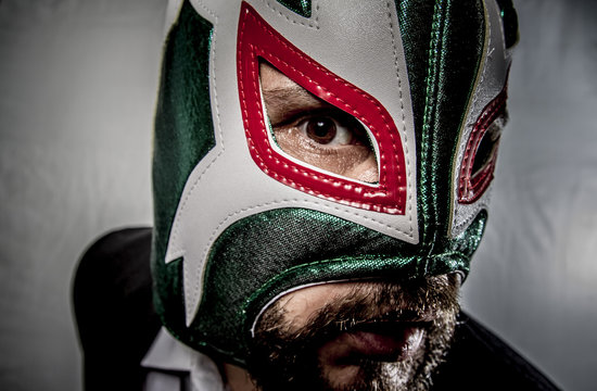 Angry businessman with mask of Mexican fighter, dressed in suit