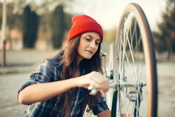 Young hipster girl install bicycle wheel