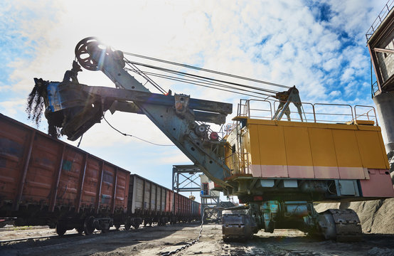 heavy excavator loading gravel into train for rail freightage
