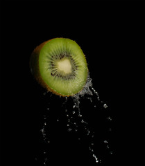 Fresh kiwi fruit splashing in the water isolated with bubbles