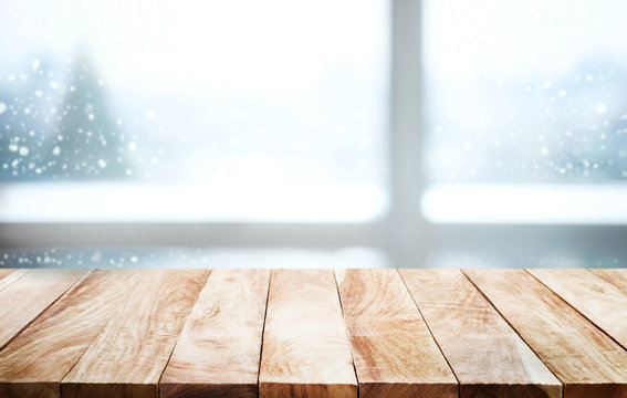 Empty wood table on blur window view with pine tree in snow fall.winter  season  background