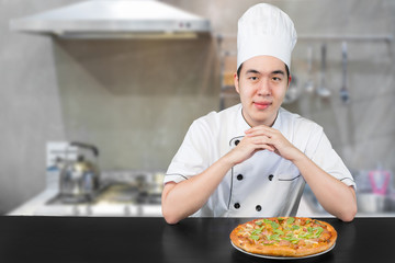 Asian young man chief in white uniform offers to you delicious pizza.