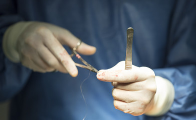 Surgeon holding a needle and thread