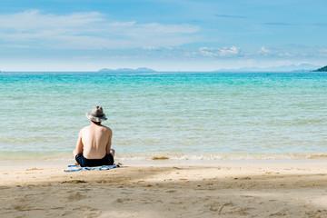 Asian man on beach rear view guy wearing summer hat