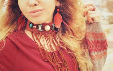 Female neck and ears with boho necklace and earrings with red feathers and brown leather, handmade jewelry