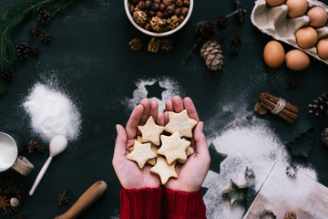 Hands holding star shaped cookies over the table with ingredients, top view