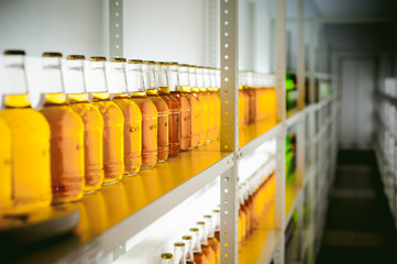 beer bottles on the shelves. many beer bottles standing in a line filled with alcohol on the shelves in the row of light