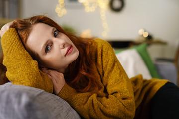 attraktive junge frau entspannt auf dem sofa in der adventszeit