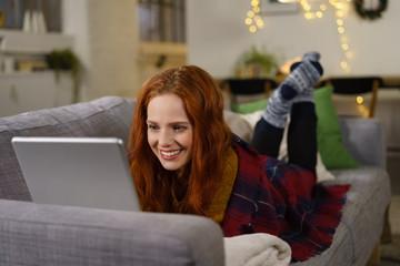frau liegt gemütlich auf dem sofa und schaut auf ihren laptop