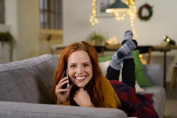 frau liegt in der adventszeit gemütlich auf dem sofa und telefoniert
