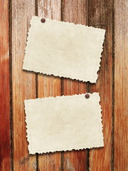 Two blank old postcard frames with pins on brown wooden boards background