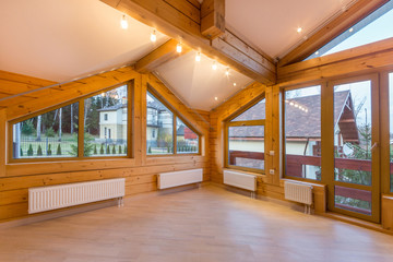Large bright empty room in a new wooden cottage