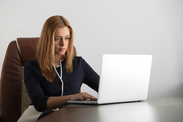 Attractive adult woman sitting at her workstation in the office