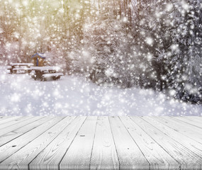 Wood table top on winter trees with snow effect background
