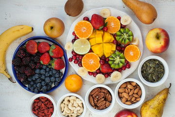 Vegan breakfast: variety of fruits, nuts and berries on the white wooden table, selective focus