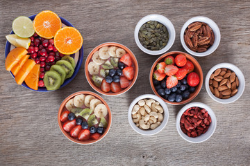 Smoothie  with fruits and berries on the grey wooden table, with variety of fruits and nuts around, top view