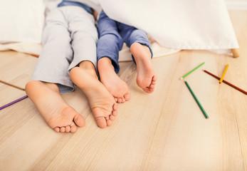 Child legs under white blanket