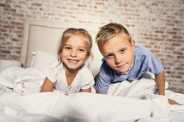 Brother and sister lying in bedroom together