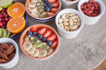 Smoothie  with fruits and berries on the grey wooden table, with variety of fruits around, selective focus