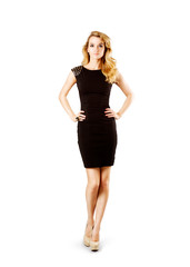 Full Length Portrait of a Sexy Blonde Woman in Little Black Fashion Dress with Hands on Hips. Gray Background. Isolated on White.