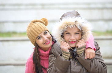 Two cheerful cute girls, one hugging  her best female friend outdoors in winter