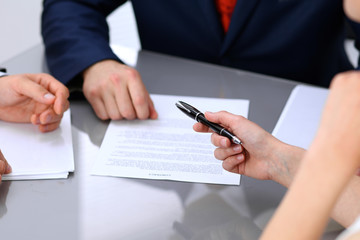 Business lady offering businessman black pen for signing a contract