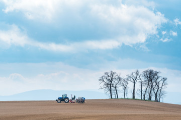 Wall Mural - Large view on the tractor harrowing the field in spring season