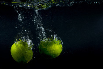 Lime splashing in water on black background