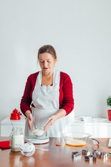 Woman measure flour on kitchen scale