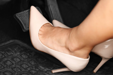 Female foot with shoe pushing on pedal of car