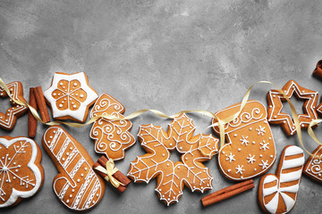 Tasty gingerbread cookies and cinnamon sticks on textured background