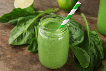 Fresh milkshake with spinach on wooden table closeup