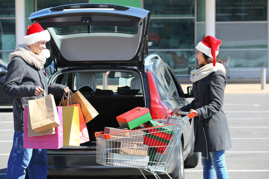 Young couple loading Christmas purchases into car trunk on shopping mall parking