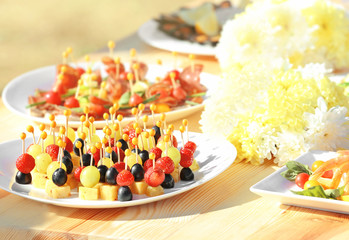 Plates with tasty snacks on wooden table, close up view