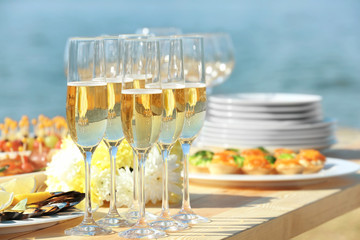 Glasses of champagne on table served for buffet catering party outdoors, close up