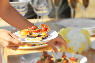 Woman choosing food during buffet catering party outdoors, close up view