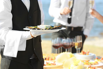 Waiter holding plate with tasty mussels, close up view