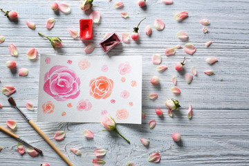 Watercolor painting with flowers on wooden table
