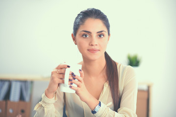 Young businesswoman sitting on the desk with cup