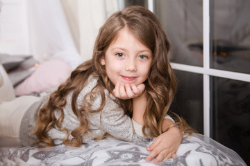 Portrait of cute little girl lying in the bed