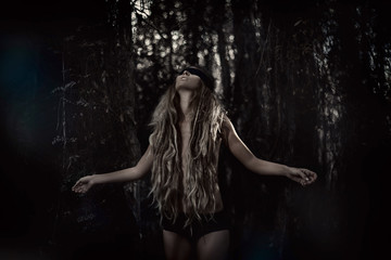 Young beautiful blindfolded woman in forest. Alone in the dark
