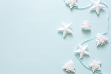 Christmas design with stars and trees on mint color background, top view