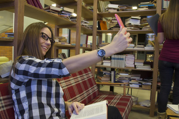 Girl in the library taking selfie by phone