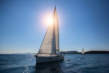 Luxury sailing ship yachts boat with white sails in the Sea.
